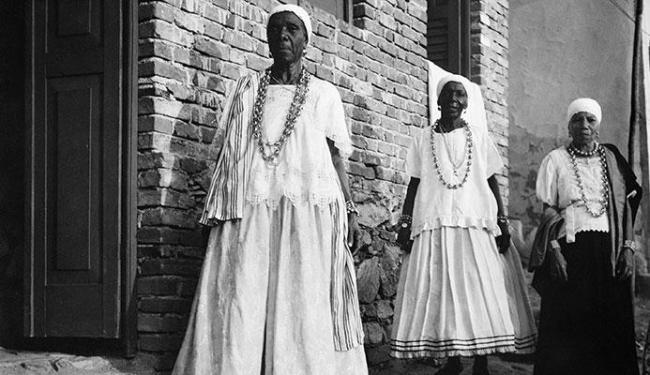Pierre Verger | Divulgação Três mulheres no Recôncavo Baiano usam bata, torço e saia numa indumentária típica de baianas