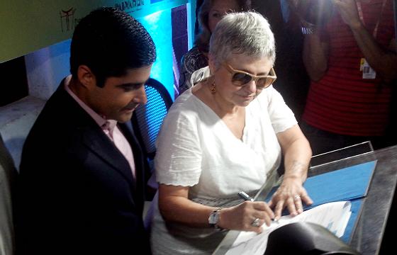 Paloma Amado assinando acordo de cessão ao lado do prefeito ACM Neto