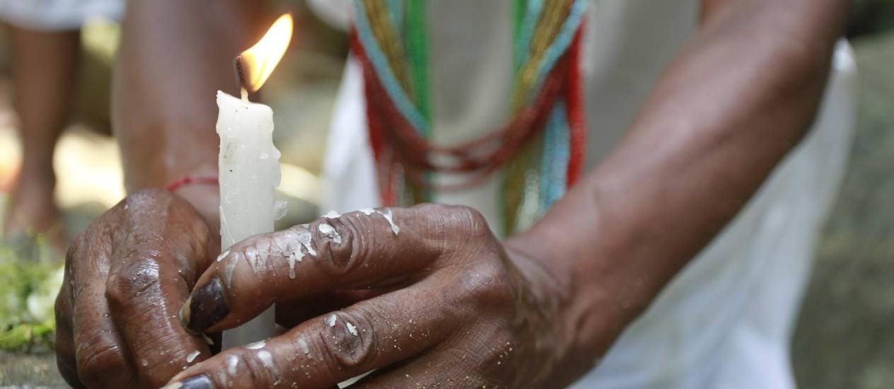 Devoção atacada: na imagem, adepta da umbanda acende vela em reverância a orixás. Culto às entidades africanas é associado ao demônio em vídeos na web - Domingos Peixoto / Agência O Globo