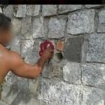 Um dos suspeitos postou foto dele próprio pichando um muro. Sinal é semelhante ao pichado na cabeça da estátua de Zumbi (Foto: Reprodução / Facebook)