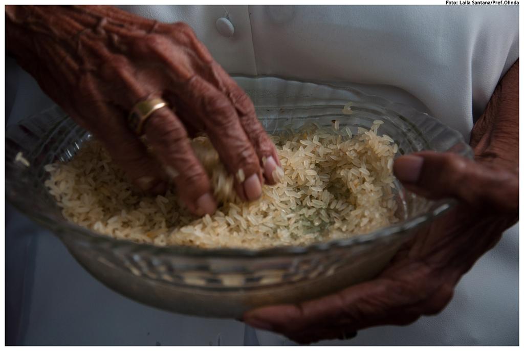 Milhares de pessoas participam da cerimônia. Na imagem, devota prepara o arroz, símbolo e alimento de Oxalá, para ser distribuído entre os participantes. Foto: Laila Santana/Pref.Olinda