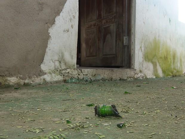 Pedaços de garrafas ficaram espalhados pelo chão do terreiro de candomblé (Foto: Reprodução/TV Paraíba)