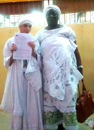 A jovem Jéssica Oliveira mostra o registro da ocorrência ao lado da mãe de santo Márcia Marçal Foto:Reprodução Facebook