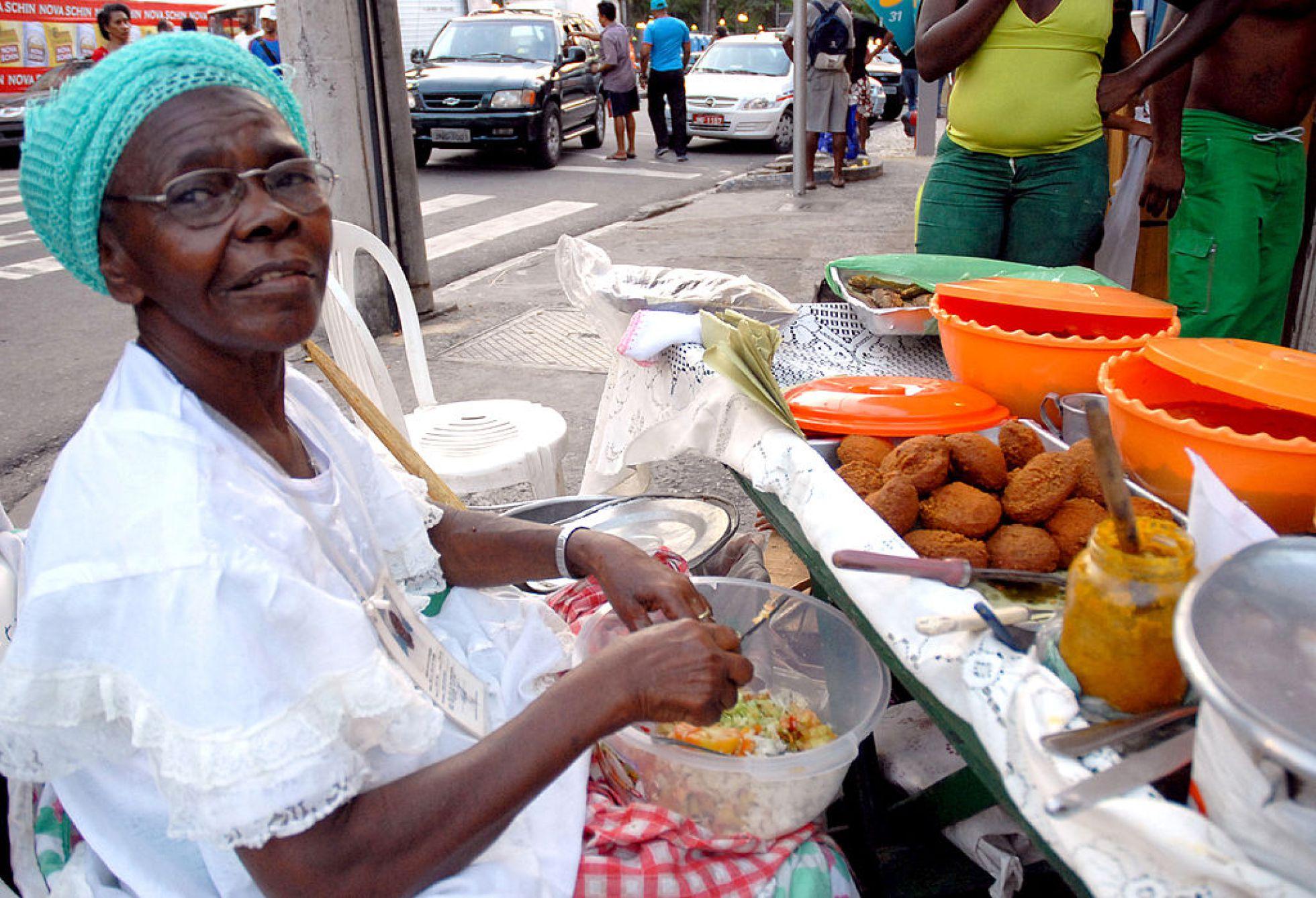 A baiana de acarajé, símbolo da ancestralidade africana na culinária brasileira. Fotos públicas