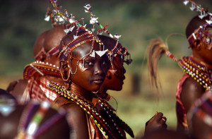 Maasai girls from Kenya attend the Eunoto ceremony – the passage of their warrior boyfriends into elderhood. Their beaded collars and headbands are designed to bounce rhythmically to enhance their body movements. Traditionally a Maasai girl is allowed to select three lovers from among the warriors. This is the one time in her life when she is allowed to enjoy freely chosen relationships. 1985