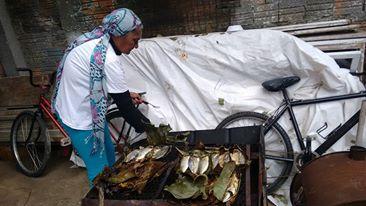 Jucélia prepara o peixe na folha de bananeira